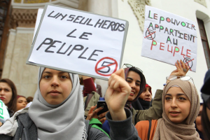 "Women hold posters reading ""Only one hero, the people,"" left, and ""The power belongs to the people"" during a demonstration in Algeria on March 8."