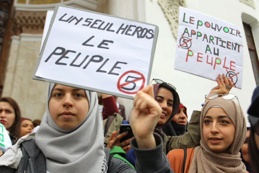 """Women hold posters reading """"Only one hero, the people,"""" left, and """"The power belongs to the people"""" during a demonstration in Algeria on March 8."""